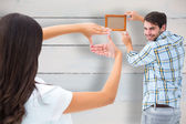 Young couple putting up picture frame — Stock Photo