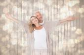 Happy couple standing with arms outstretched — Stock Photo