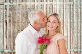 Man kissing his wife on the cheek with roses — Stock Photo