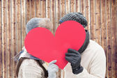 Couple in warm clothes holding red heart — Stock Photo