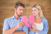 Couple holding two halves of broken heart — Stock Photo