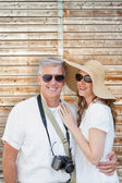 Vacationing couple against wooden background — Stock Photo