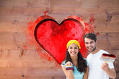 Couple painting together against red heart — Stock Photo