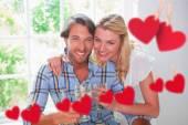 Couple enjoying white wine together against hearts — Stock Photo