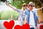 Couple going for a bike ride against hearts — Stock Photo