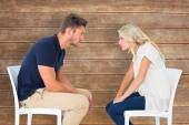 Young couple sitting in chairs arguing — Stock Photo