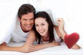 Couple lying on bed against red heart — Stock Photo