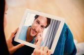 Woman using tablet with man looking at camera — Stock Photo