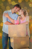 Couple leaning on boxes with piggy bank — Foto de Stock