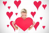 Blonde showing red heart — Stock Photo