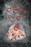 Hand bursting through paper against heart — Stock Photo