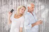Happy couple texting on their smartphones — Stock Photo