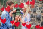 Couple by railings against hearts — Stock Photo