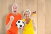 German couple cheering at camera holding ball — Stock Photo