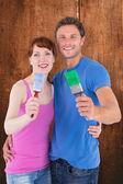 Couple both holding paint brushes — Stock Photo