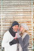 Couple in winter fashion holding mugs — Stock Photo