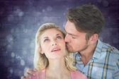 Handsome man kissing girlfriend on cheek — Stock Photo