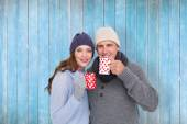 Couple in warm clothing holding mugs — Stock Photo