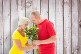 Mature man offering his partner flowers — Stock Photo