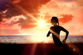 Woman jogging against sunrise over magical sea — Стоковое фото