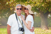 Vacationing couple against trees and meadow — Stock Photo