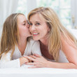 Daughter kissing her mother on the cheek in the bed  — Stock fotografie #68953597
