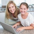 Happy mother and daughter using laptop together — Stock Photo #68955785