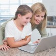 Happy mother and daughter using laptop together — Stock Photo #68956235