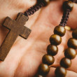 Hand holding wooden rosary beads — Stock Photo #68956417