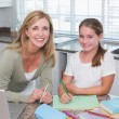 Happy mother helping daughter doing homework — Stock Photo #68957881