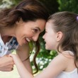 Mother and daughter smiling at each other — Stock Photo #68958083