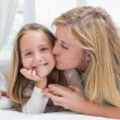 Mother kissing her daughter on the cheek in the bed — Stock Photo #68958315