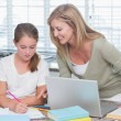 Happy mother helping daughter doing homework — Stock Photo #68958653