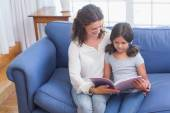 Happy mother and daughter reading book — Stockfoto