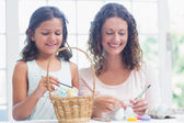 Happy mother and daughter painting easter eggs  — Stock Photo