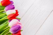 Colorful tulips on wooden table — Stock Photo