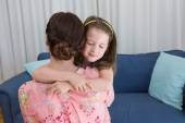 Little girl with her mother on sofa — Stock Photo