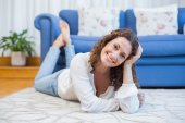 Smiling woman lying on the floor — Stock Photo