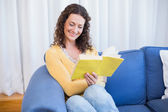 Brunette relaxing on couch and reading book — Stock Photo