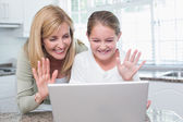 Mother and daughter talking with someone with the laptop — Stock Photo