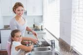 Mother and daughter washing up — Stock Photo