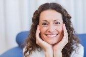 Smiling woman sitting on the couch — Stock Photo