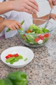 Mother and daughter preparing salad — Stock Photo