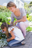 Mother and daughter tending to flowers — Stock Photo