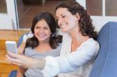 Happy mother and daughter sitting on the couch and taking selfie — Stock Photo