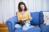 Brunette relaxing on couch and reading magazine — Stock Photo