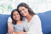 Happy mother and daughter smiling at camera — Stock Photo