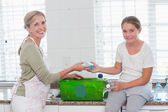 Mother and daughter putting bottles in recycling box — Stock Photo