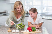 Mother and daughter preparing salad together — Stockfoto