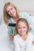 Smiling mother brushing her daughters hair  — Stock Photo